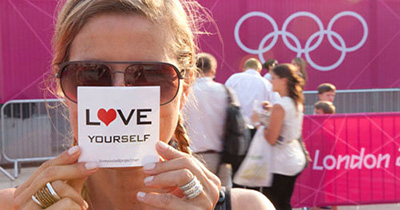 Woman holding a Love Yourself Project sticker